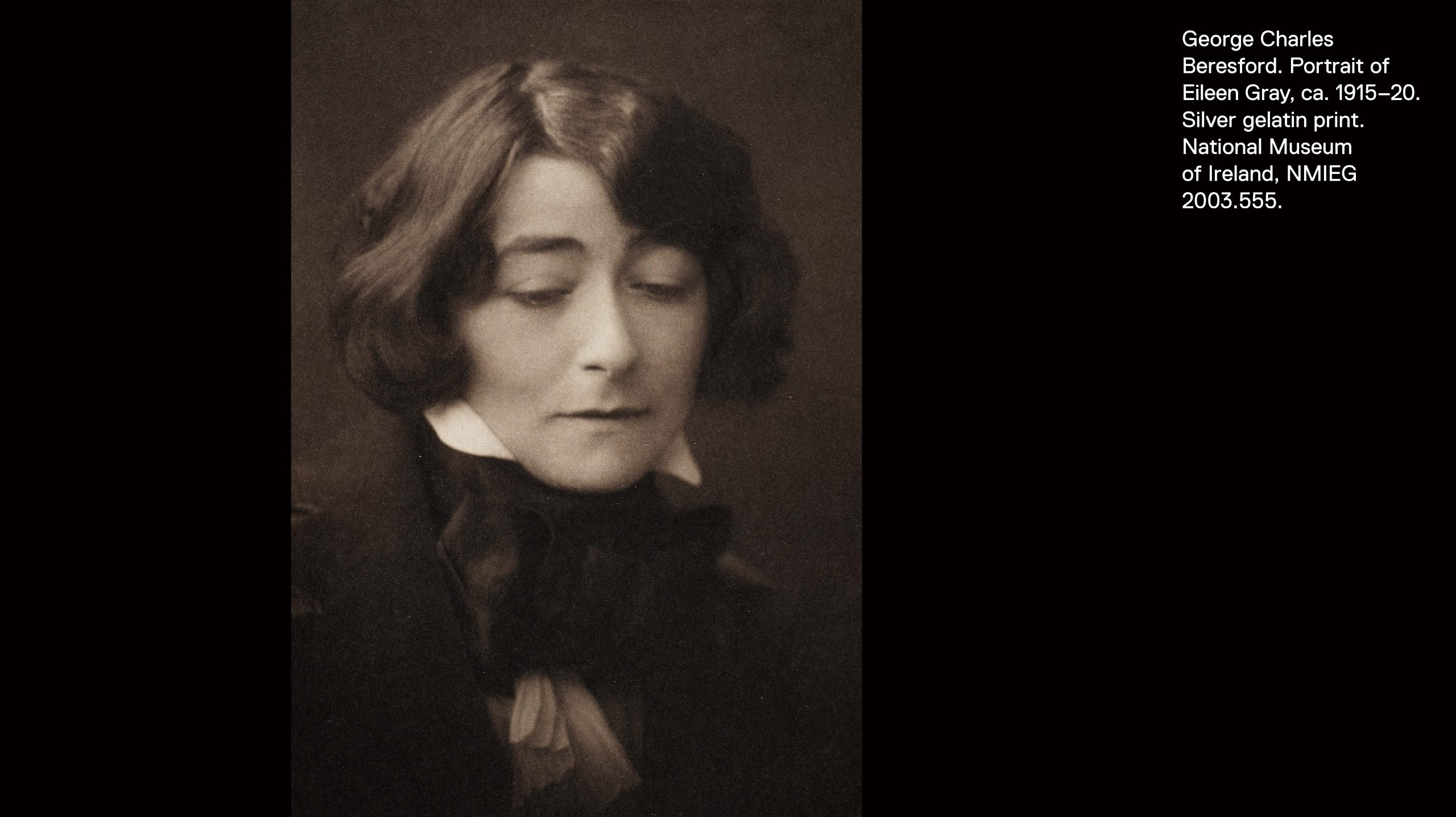 Bust-length portrait of Eileen Gray with chin-length cropped hair wearing a dark jacket, high collar, and large silk necktie.