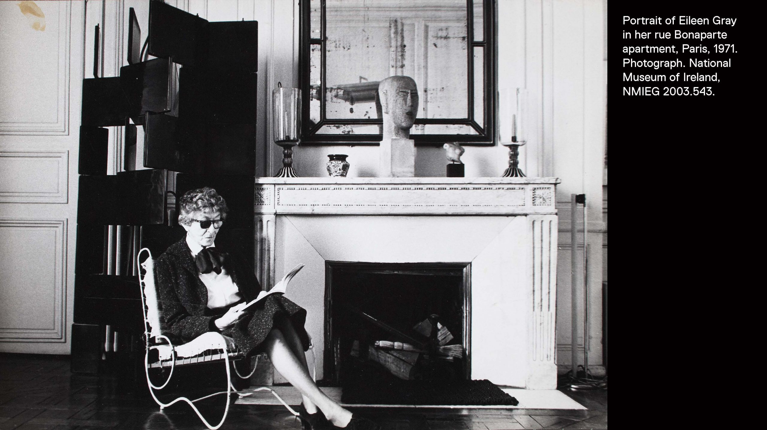 Eileen Gray sitting in a chair she designed in front of one of her lacquer block screens and a fireplace with sculptures.