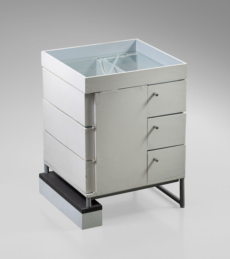 Installation image of a small white cabinet with three pivoting drawers.