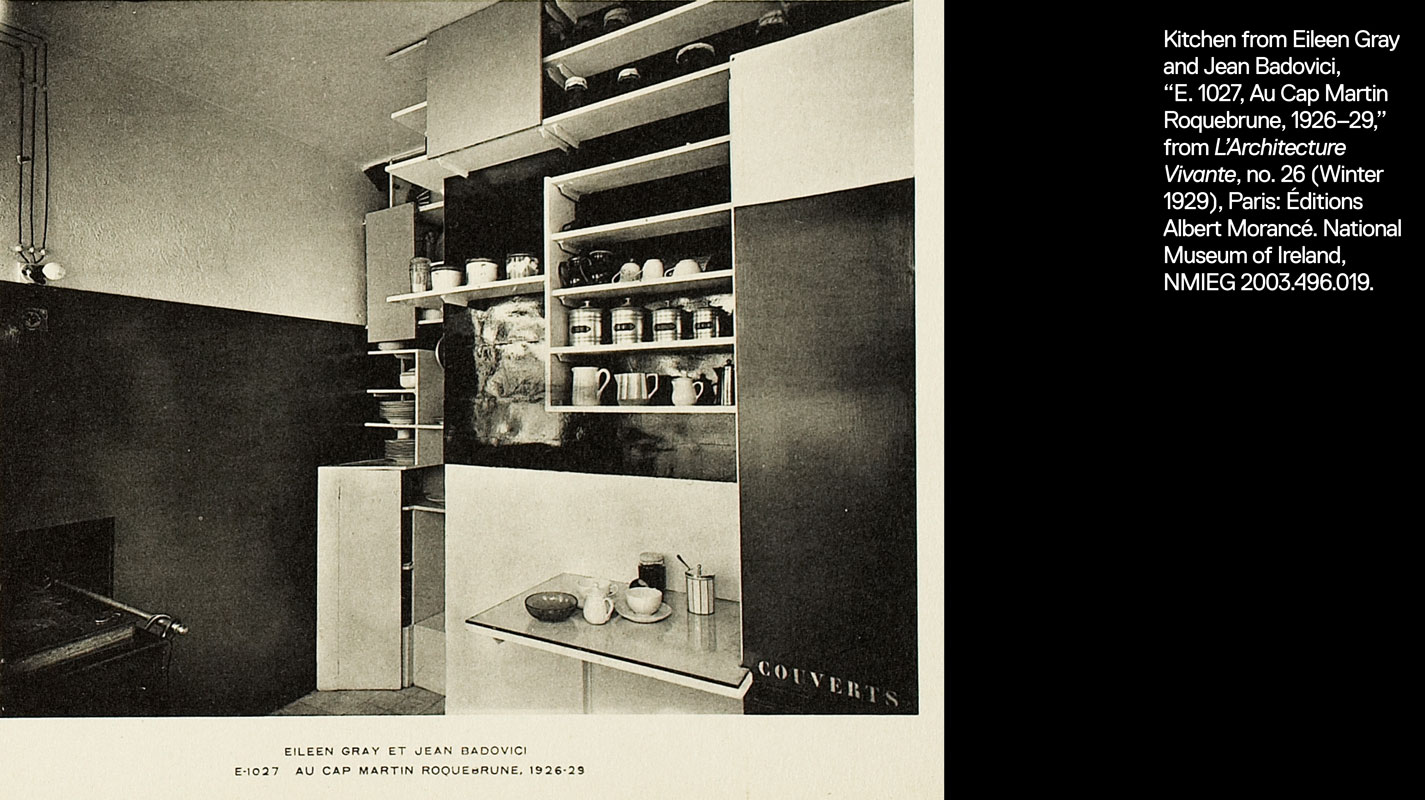 "E 1027 kitchen with shelves full of dishes and small containers. One cabinet has word ""Couverts"" stenciled on the front."