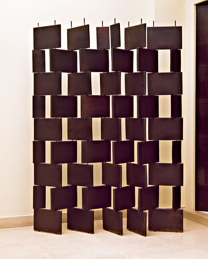 Image of a wooden screen created from 54 panels stacked askew.