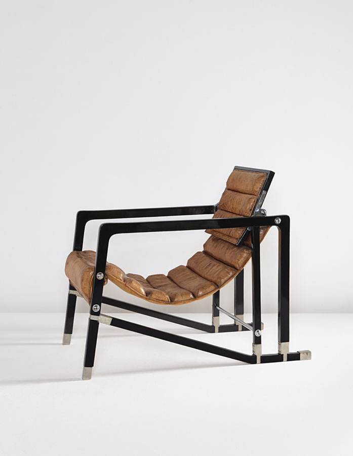 Installation image of a tan leather and black metal armchair.